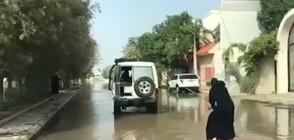 СТРАННА ГЛЕДКА: Жена с бурка сърфира по наводнена улица (ВИДЕО)