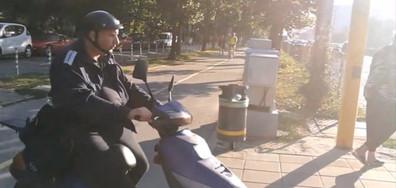 Униформен полицай със скутер по тротоара
