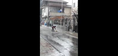 Метене на улицата по време на обилен дъжд