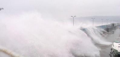 Огромна вълна се разбива във вълнолома и залива кола